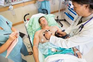 High angle view of doctor defibrillating male patient while nurs
