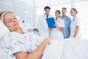 Sleeping patient with doctors behind in hospital room