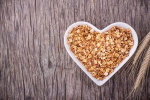 Home caramel granola in a white ceramic dish shape of heart