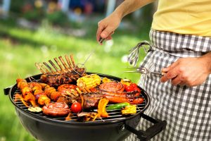 Man cooking meat on barbecue for family dinner